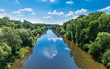 Watercourse of Luznice river in Tabor city, Southern Bohemia, Europe. Scenic landscape with water surface and mirroring a blue sky with white clouds and banks with lush tree vegetation.