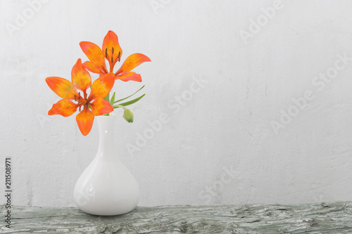 orange lily in vase on white background