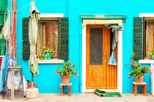 Poster Turquoise Blue aqua colored house with flowers and plants. Colorful house in Burano island near Venice, Italy