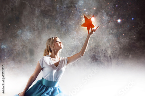 Photo Young attractive woman reaching for the star