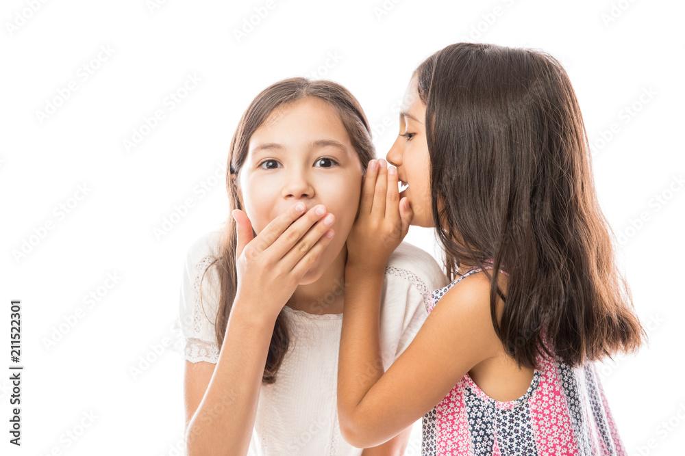 Fototapeta Younger sister whispering news to older sister's ear