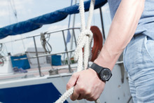 Man Hand With Boat Rope. Yachtsman Tying Sea Knot. Black Watches On Man Hand Holding Rope With Knot. Close Up Hands