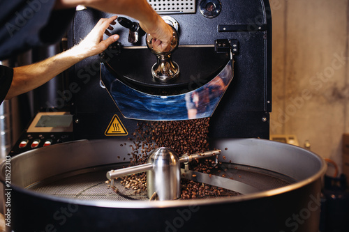 Slika na platnu Freshly roasted coffee beans pouring from a large coffee roaster into the cooling cylinder
