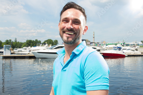 Fotografía  Portrait of smiling happy yachtsman on marina with boat background