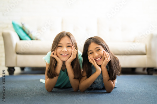 Fotografie, Tablou Portrait of two sisters lying on the floor in living room smiling