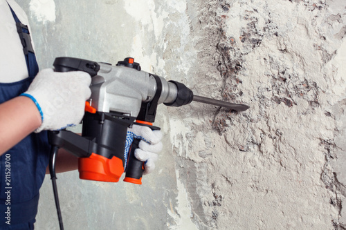 Carta da parati The builder with hammer drill perforator equipment making hole in wall at construction site