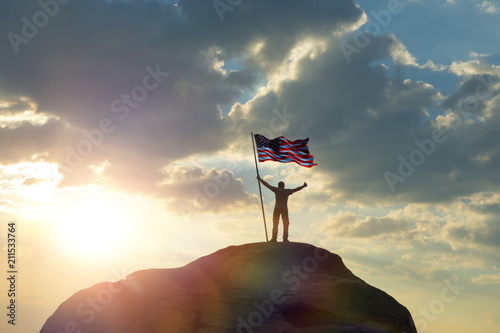 Photo  the man is standing on the top of the mountain, holding his hands up with the flag of the US america against the sunset