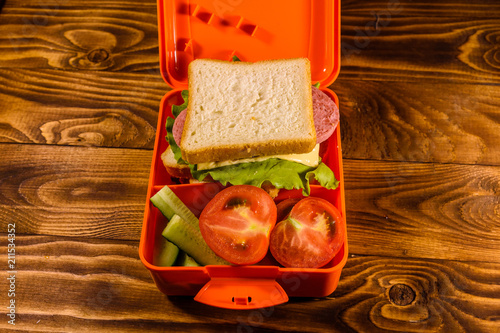 Foto op Canvas Assortiment Lunch box with sandwich, cucumbers and tomatoes on wooden table