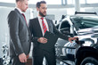 Professional salesperson selling car at dealership to buyer