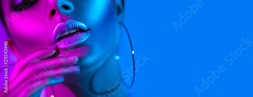 High fashion model woman in colorful bright neon lights posing in studio. Beautiful sexy girl, trendy glowing makeup, metallic silver lips
