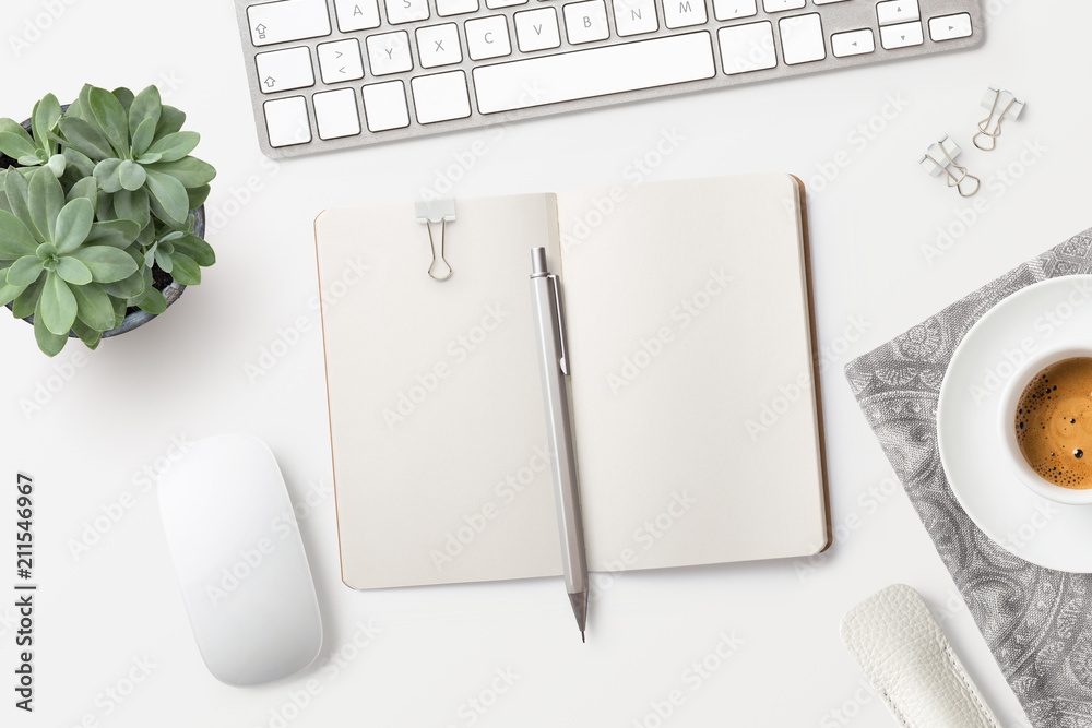Fototapeta bright minimalist workspace / desktop with blank open notebook, office supplies, coffee and succulent plant on a white background - top view, copyspace