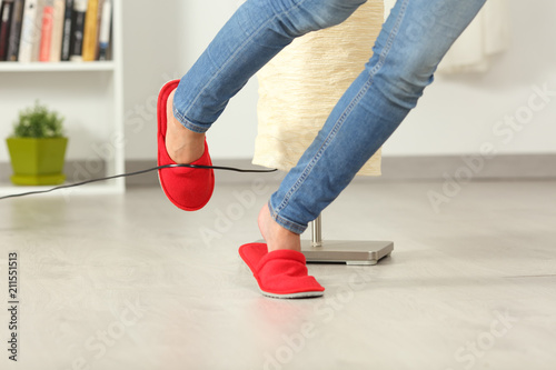 Fotografie, Obraz  Woman stumbling with an electrical cord at home