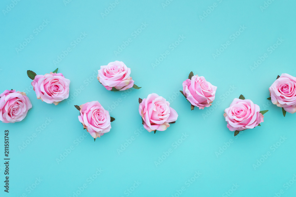 Row of satin pink rose buds on turquoise pastel background. Top view.