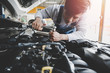 Young Asian car mechanic working at service center repair