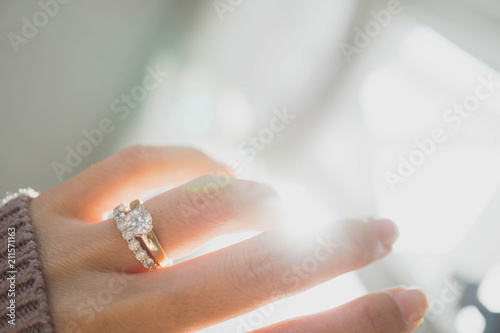 Obraz na plátne Close up of elegant diamond ring on woman finger with dark pink sweater winter clothe and sunlight tone