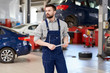 Portrait of modern bearded mechanic holding wrench standing confidently and looking away while working in car service and repair center, copy space