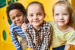 Leinwandbild Motiv Colorful portrait of three happy kids posing looking at camera while having fun playing in children center