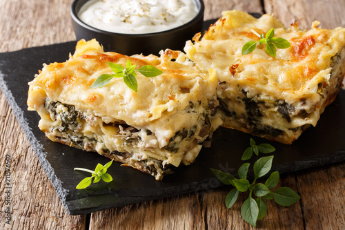 Casserole of lasagna with chicken breast, wild mushrooms, cheese, herbs and bechamel sauce close-up on a slate plate on a wooden table. horizontal