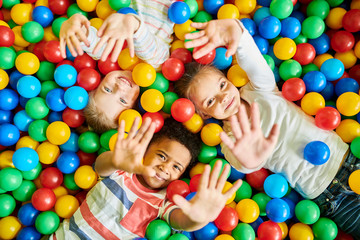 Above view portrait of three happy little kids in ball pit smiling at camera ...