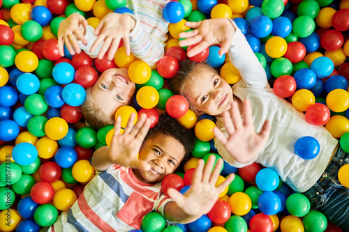 Above view portrait of three happy little kids in ball pit smiling at camera raising hands while having fun in children play center, copy space