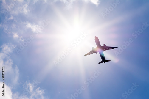 Photo The plane flies in the sky against the sun.