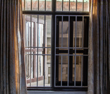 A Barred Window Open To The St...