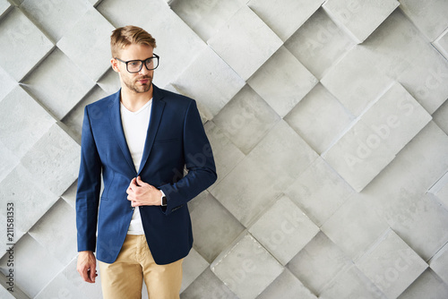 Fotografía  Waist up portrait of male standing and touching jacket