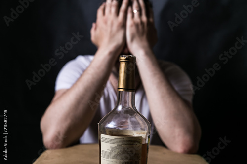 Staande foto Bar bottle of alcohol with drinking man. Serious unhappy sad man sitting. alcohol addiction. social problems