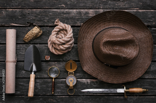 Fototapeta Gold ore, compass, loupe, dagger, shovel, rope and old scroll document on adventurer or explorer wooden table