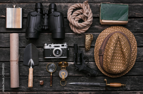Compass, binoculars, film photo camera, loupe, dagger, handgun, diary book, shovel, rope, gold ore and old scroll document on adventurer or explorer wooden table Canvas Print