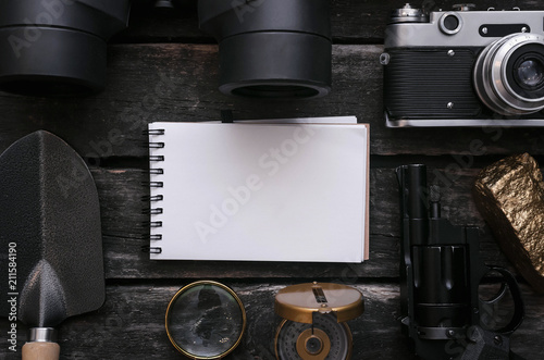 Blank page notepad, binoculars, film photo camera, compass, magnifying glass and shovel on adventurer wooden table Canvas Print