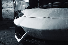 Beautiful Fast White Pure Aggressive With Rain Drops Car Standing Outside In The Garage In The Evening