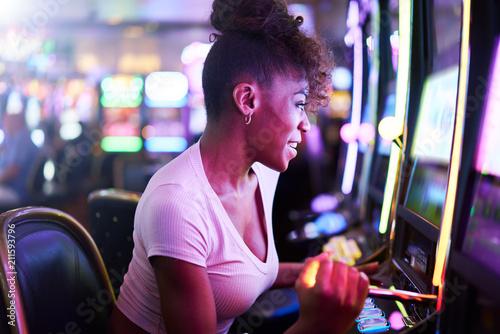 фотография  woman having fun playing slot machine at casino