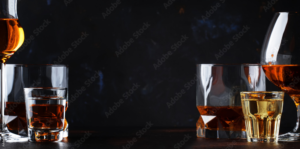 Fototapeta Set of strong alcoholic drinks in glasses and shot glass in assortent: vodka, rum, cognac, tequila, brandy and whiskey. Dark vintage background, selective focus