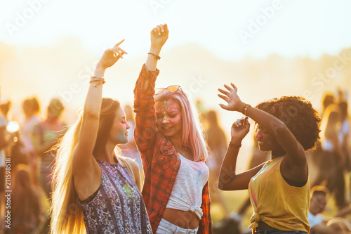 Fotomural Multiethnic girls covered in colorful powder dancing and celebrating summer holi
