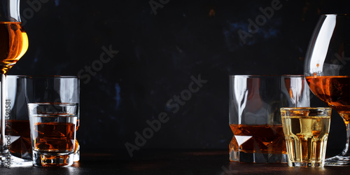 Poster Alcohol Set of strong alcoholic drinks in glasses and shot glass in assortent: vodka, rum, cognac, tequila, brandy and whiskey. Dark vintage background, selective focus