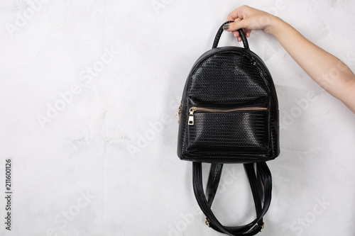 Obraz Female hand holding small leather backpack against white wall. Empty space - fototapety do salonu