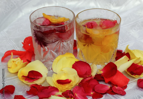 Poster  Glass with cold water, drops of dew and rose petals on table