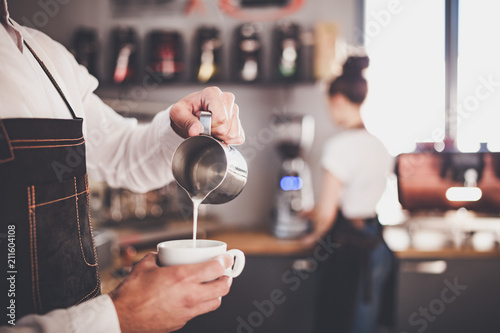 Fotografie, Obraz  Professional barista pouring milk make coffee latte art