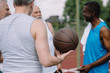 selective focus of group of multiracial old sportsmen with basketball ball on playground