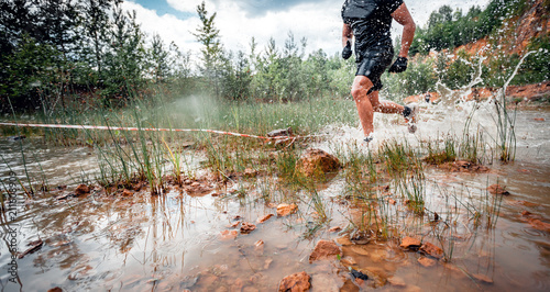 Cross country trail runner moving through water on rural road