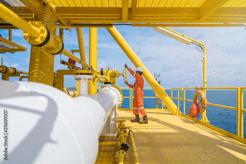 Vászonkép Offshore oil rig worker wear helmet gloves safety glass and coverall suite opening valve at oil and gas central processing platform, maintenance and service jot at offshore power and energy industry