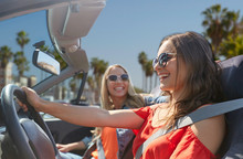 Summer Holidays, Road Trip, Vacation, Travel And People Concept - Happy Young Women Driving In Convertible Car And Laughing Over Venice Beach Background In California