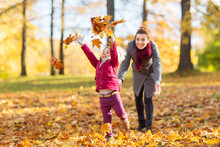 Family, Season And People Concept - Happy Mother And Little Daughter Playing With Autumn Leaves At Park