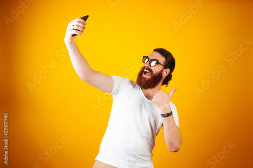Fotografía Young Cheerful man taking a selfie on his smartphone wearing a white T-shirt and earpods