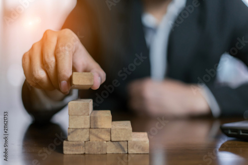 Fotografía  Businessman planing and strategy putting wooden blocks risk or success project hands control stack of danger tower challenge game building construction protect at office