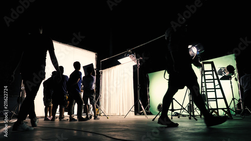 Photo  Behind the scenes of TV commercial movie film or video shooting production which crew team and camera man setting up green screen for chroma key technique in big studio
