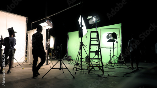 Behind the scenes of TV commercial movie film or video shooting production which crew team and camera man setting up green screen for chroma key technique in big studio Fototapete