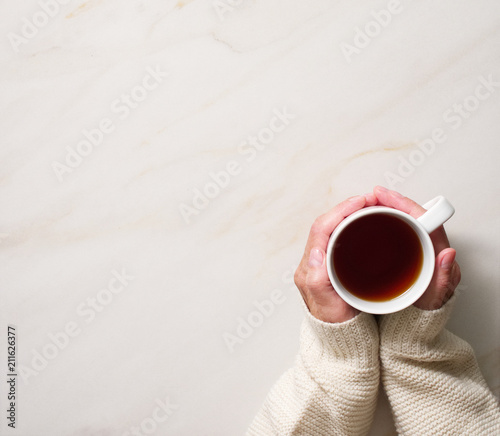 Foto op Plexiglas Chocolade Woman holding cup of hot tea on stone beige table, hands in warm sweater with mug, winter morning concept, top view