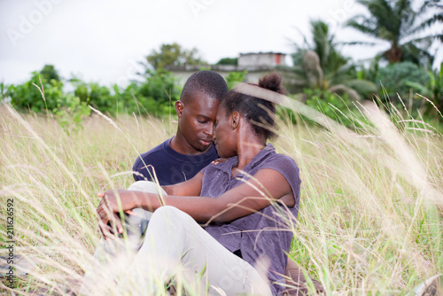 happy young couple in love relaxes sitting in the grass in summer Poster